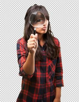 Латинская девушка смотрит через увеличительное стекло