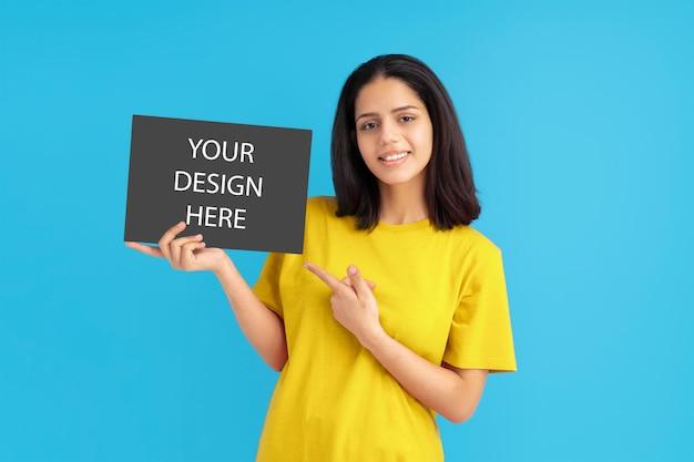 노란색 티셔츠 포스터를 들고 손가락을 가리키는 라틴 여자, 모형