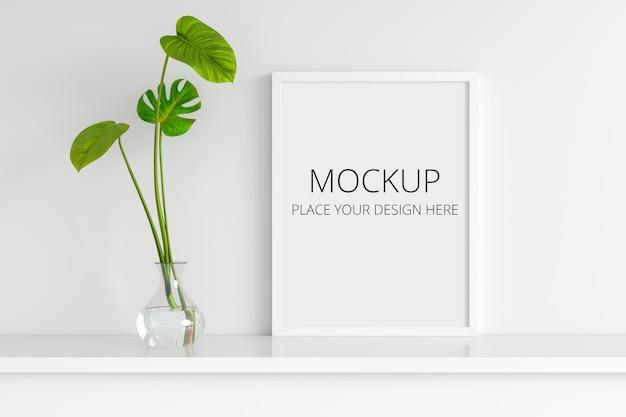額縁モックアップ3dレンダリングでガラスの花瓶の葉