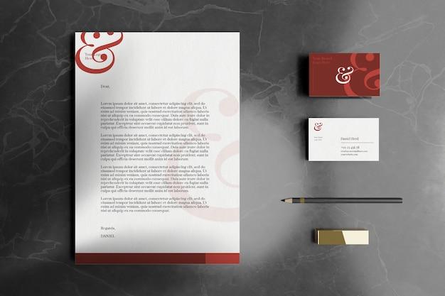 Фирменный бланк формата а4 с визитной карточкой и макетом канцелярских товаров на мраморном полу