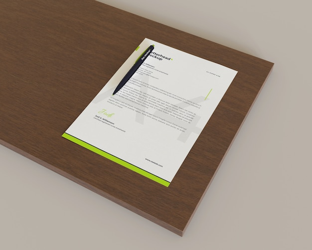Letterhead with a pen above dark brown wood look on the right view
