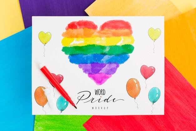 Взгляд сверху покрашенного радугой сердца на бумаге с воздушными шарами для гордости lgbt