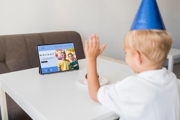 Маленький мальчик празднует дома с планшетом