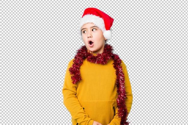 Мальчик празднуя рождество нося шляпу santa изолировал быть сотрясенным из-за что-то она видела.