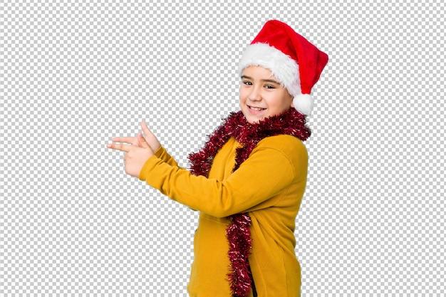Мальчик празднуя рождество нося шляпу santa изолировал возбужденный указывать с указательными пальцами прочь.