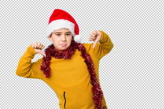 Мальчик празднуя рождество нося изолированную шляпу santa чувствует гордый и самоуверенный, пример для следования.