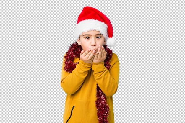 Мальчик празднуя рождество нося шляпу santa изолировал складывая губы и держа ладони для посылки воздушного поцелуя.
