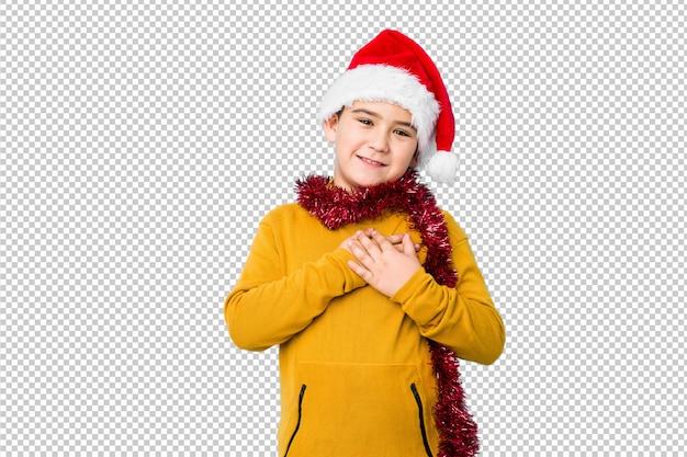 고립 된 산타 모자를 쓰고 크리스마스를 축 하하는 어린 소년 손바닥에 가슴을 누르면 친절 한식이있다. 사랑 개념.