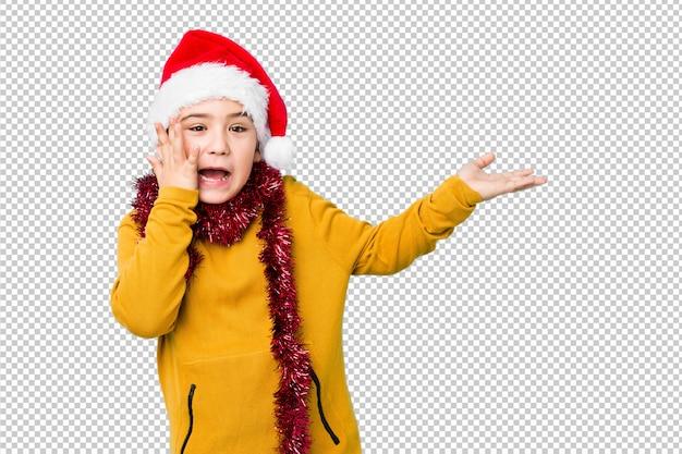 Мальчик празднуя рождество нося изолированную шляпу santa держит космос экземпляра на ладони, держит руку над щекой. поражен и восхищен.