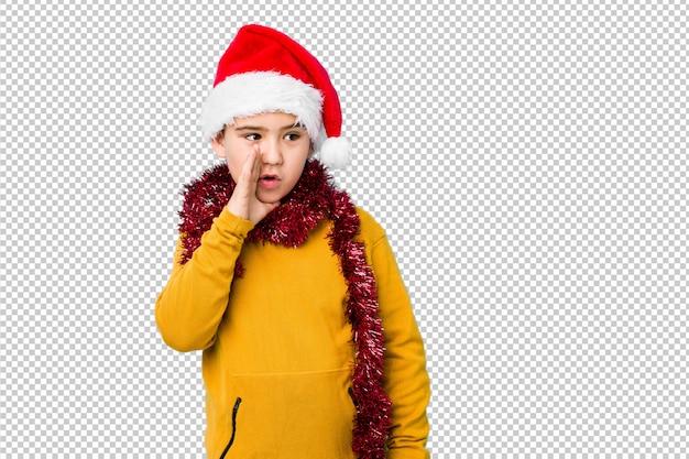 Мальчик празднуя рождество нося изолированную шляпу santa говорит секретные горячие новости торможения и смотрит в сторону