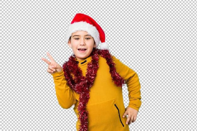 Мальчик празднуя рождество нося шляпу santa изолировал радостный и беспечальный показывать символ мира с пальцами.