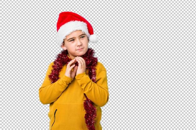 Мальчик празднуя рождество нося шляпу santa изолировал составлять план в разуме, настраивающ идею.