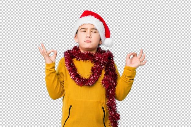 孤立したサンタ帽子をかぶってクリスマスの日を祝う小さな男の子は、懸命に働いた後リラックスし、ヨガを実行しています。