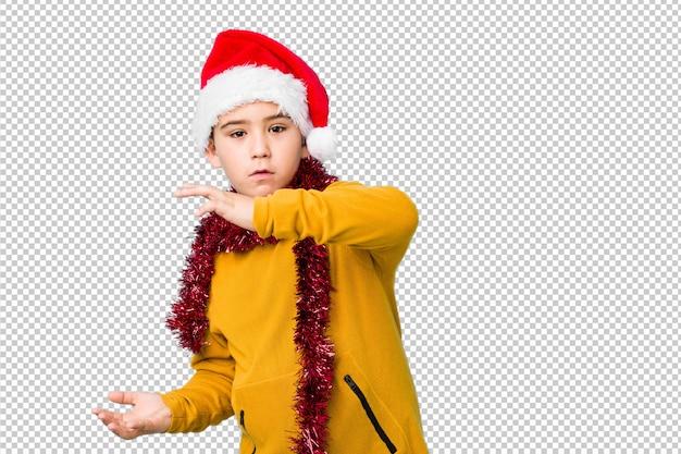 Мальчик празднуя рождество нося шляпу santa изолировал сотрясенный и изумленный держащ космос экземпляра между руками.
