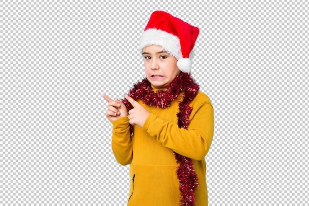 Мальчик празднуя рождество нося шляпу santa изолировал сотрясенный указывать с указательными пальцами к космосу экземпляра.
