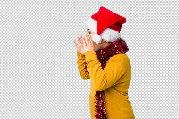 Маленький мальчик, празднование рождества, носить шляпу санта изолированные крики громко, держит глаза открытыми и руки напряженными.