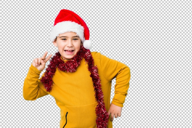 Мальчик празднуя рождество нося шляпу santa изолировал показывать знак победы и широко усмехаться.