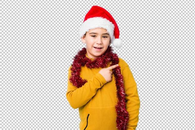 Мальчик празднуя рождество нося шляпу santa изолировал усмехаться и указывать в сторону, показывая что-то на пустом пространстве.