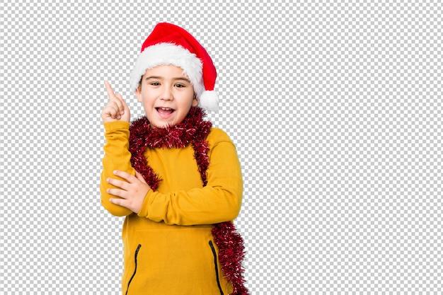 Маленький мальчик, празднование рождества, носить шляпу санта изолированы, улыбаясь, весело указывая с указательным пальцем прочь.