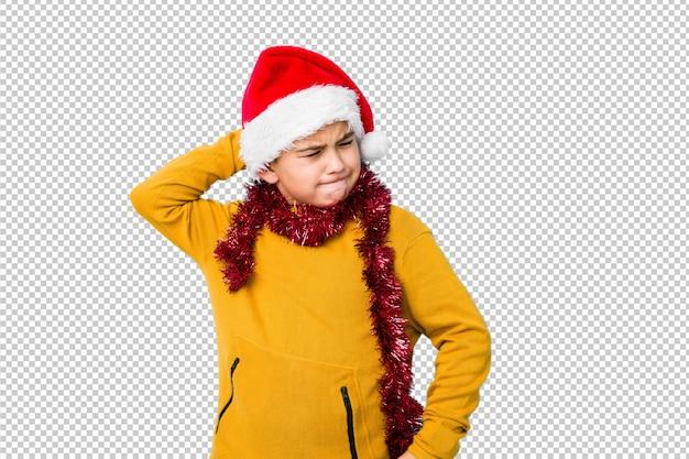 Мальчик празднуя рождество нося шляпу santa изолировал касаться задней части головы, думая и делая выбор.