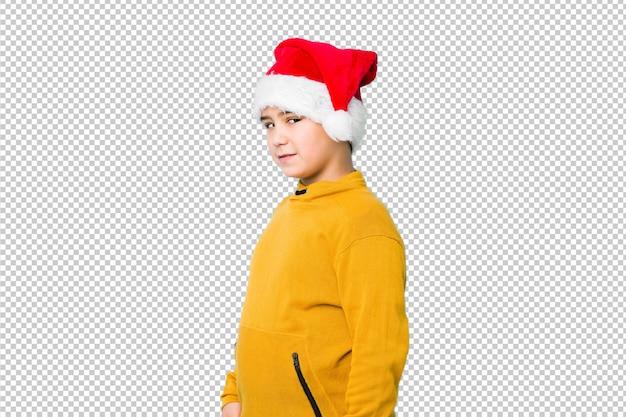 산타 모자를 쓰고 크리스마스를 축 하하는 어린 소년 옆으로 웃 고 명랑 하 고 쾌적 보인다.