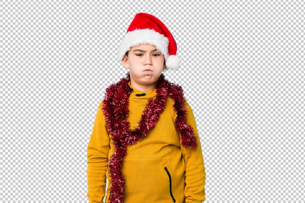Little boy celebrating christmas day wearing a santa hat blows cheeks, has tired expression. facial expression concept.