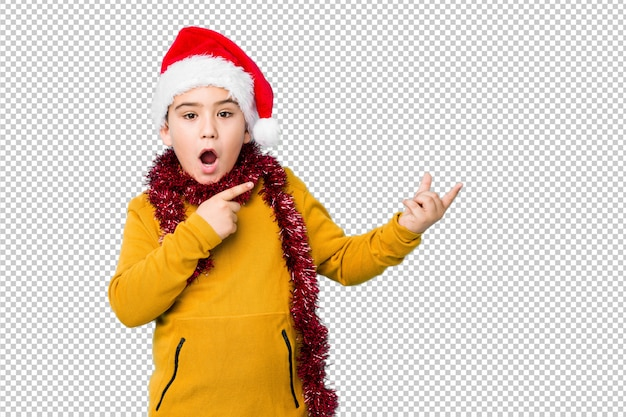 Little boy celebrating christmas day wearing a santa hat isolated excited holding a copy space on palm.