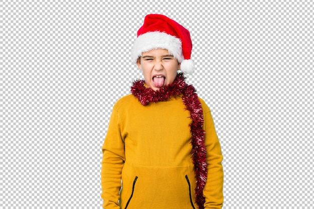 Little boy celebrating christmas day wearing a santa hat isolated funny and friendly sticking out tongue.
