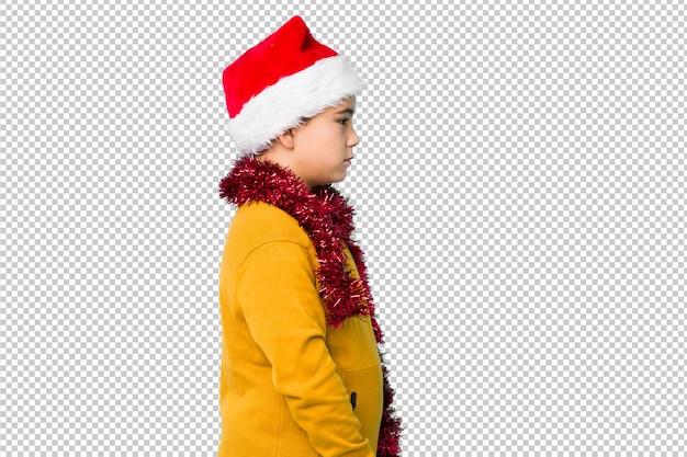 Little boy celebrating christmas day wearing a santa hat isolated gazing left, sideways pose.