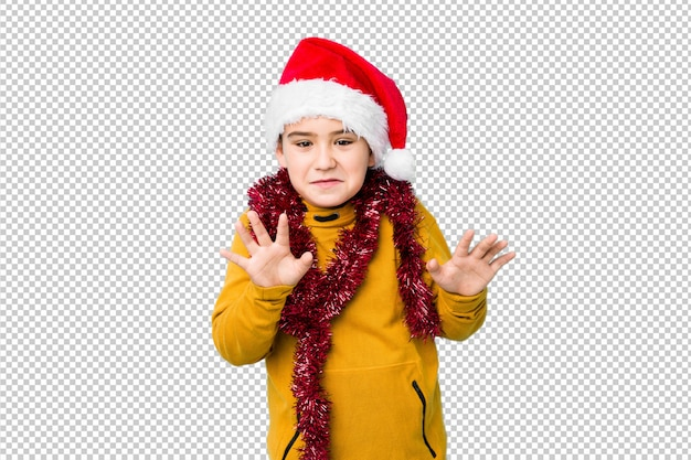 Little boy celebrating christmas day wearing a santa hat isolated rejecting someone showing a gesture of disgust.