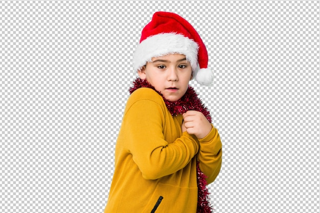 Little boy celebrating christmas day wearing a santa hat isolated scared and afraid.