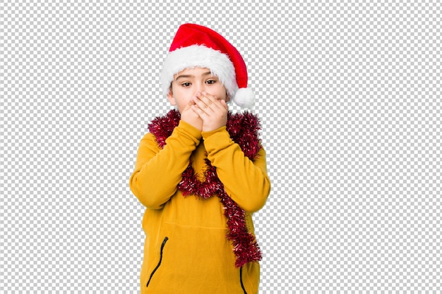 Little boy celebrating christmas day wearing a santa hat isolated shocked covering mouth with hands.