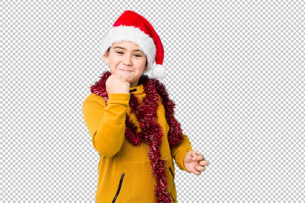 Little boy celebrating christmas day wearing a santa hat isolated showing fist to camera, aggressive facial expression.