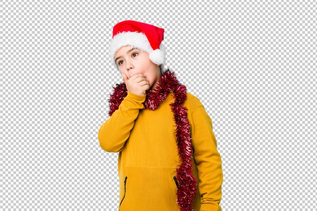 Little boy celebrating christmas day wearing a santa hat isolated thoughtful looking to a copy space covering mouth with hand.
