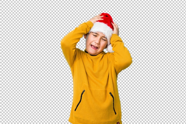 Little boy celebrating christmas day wearing a santa hat laughs joyfully keeping hands on head. happiness concept.