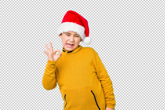 Little boy celebrating christmas day wearing a santa hat winks an eye and holds an okay gesture with hand.