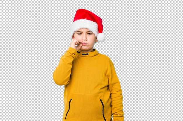 Little boy celebrating christmas day wearing a santa hat with fingers on lips keeping a secret.