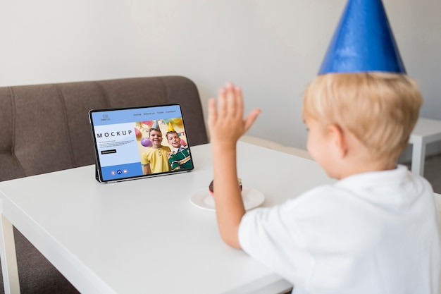 Little boy celebrating at home with tablet