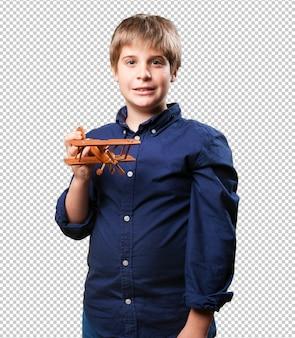 나무 복 엽 비행기 장난감을 들고 어린 소년