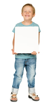 Little boy holding blank paper board studio portrait