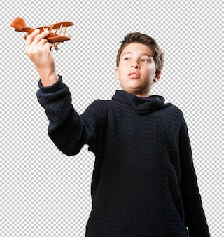 Little boy with a wooden plane on white