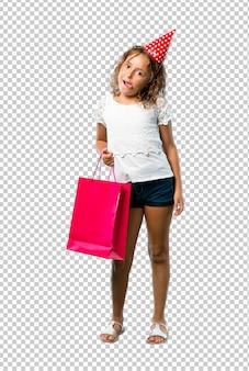 Маленькая девочка на вечеринке по случаю дня рождения держит мешок подарка, показывая язык на камеру, имея смешной взгляд