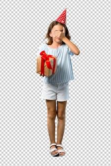 Маленькая девочка на вечеринке по случаю дня рождения держа подарок покрывая глаза руками