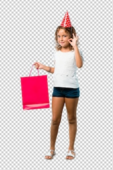 Little girl at a birthday party holding a gift bag showing an ok sign with fingers