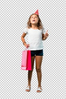 Little girl at a birthday party holding a gift bag standing and thinking an idea