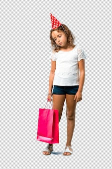 Little girl at a birthday party holding a gift bag unhappy and frustrated with something