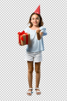 Little girl at a birthday party holding a gift presenting and inviting to come