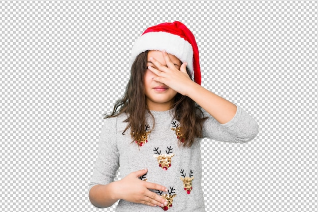Little girl celebrating christmas day blink at the camera through fingers, embarrassed covering face.