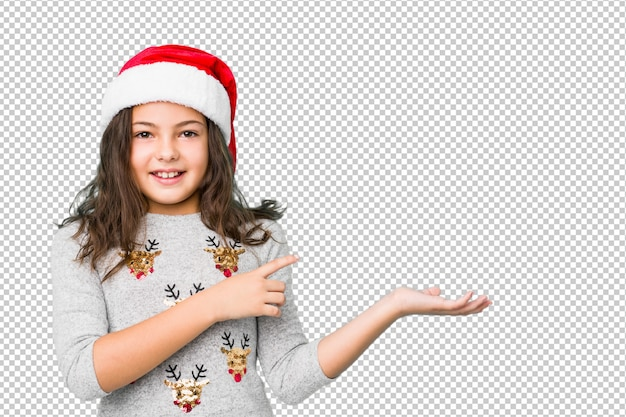 Little girl celebrating christmas day excited holding a copy space on palm.