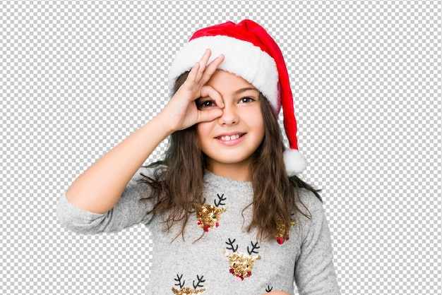 Little girl celebrating christmas day excited keeping ok gesture on eye.